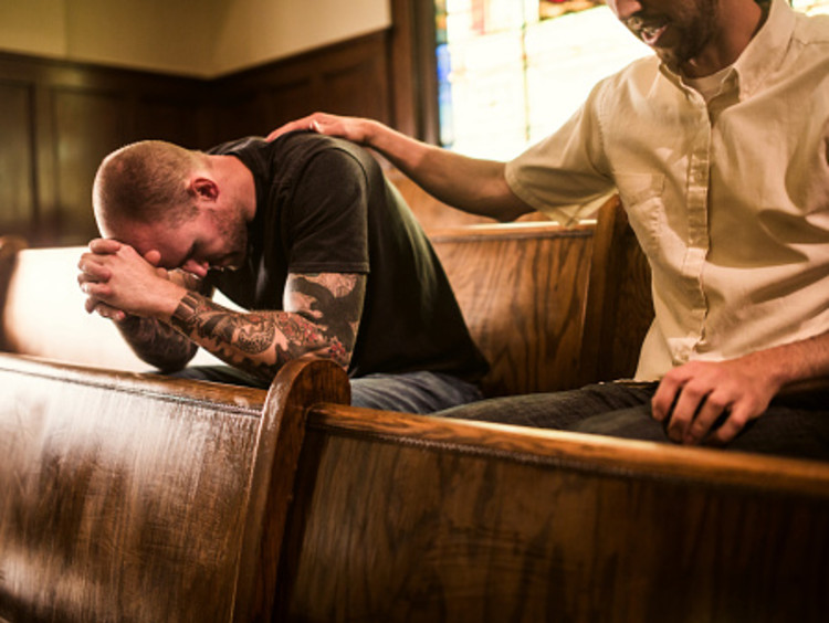 Men praying together as part of Christian practices