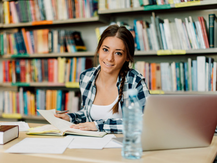 female student studying for college exams in library