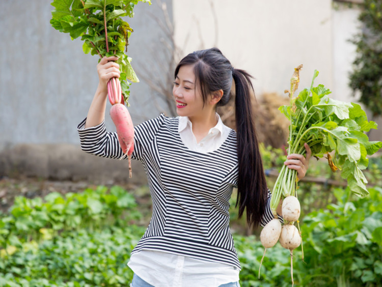 girl in a garden holding up two different vegetables