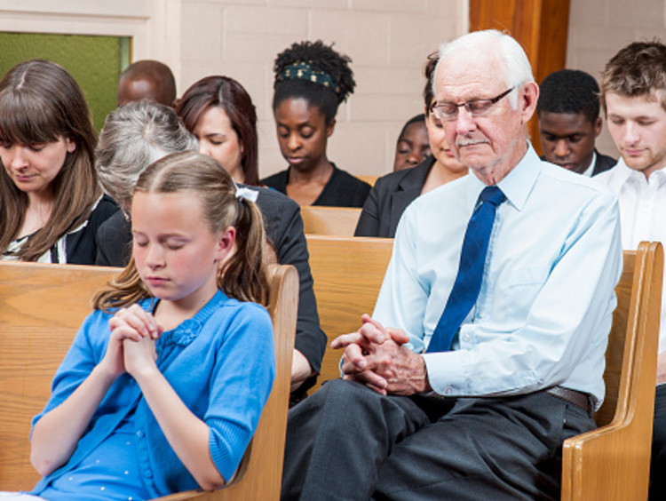 Community church pews full of people of all ages and races with heads bowed and hands clasped