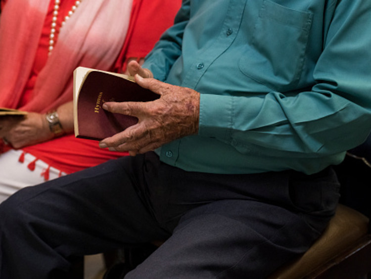 Older couple sitting next to each other open hymnals in a Christian community church