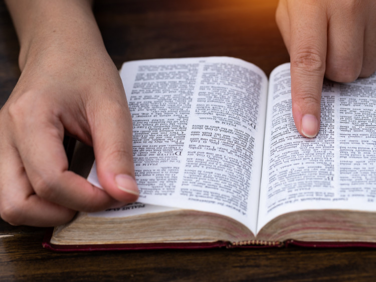 finger pointing at a Bible