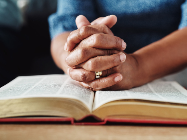 Hands praying over Bible