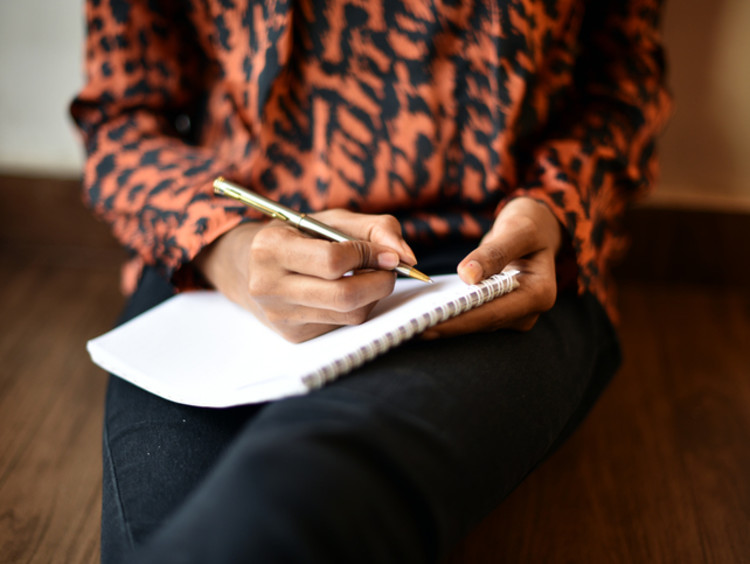 woman writing on notebook