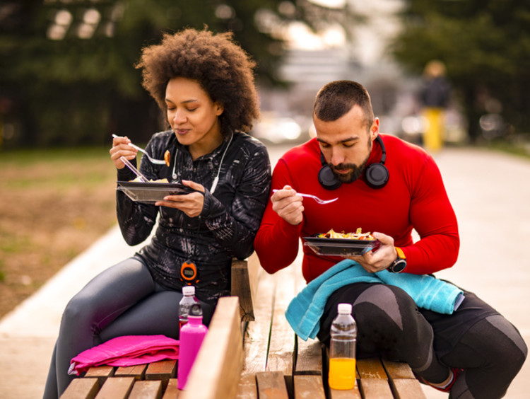 Two athletes eating on a bench