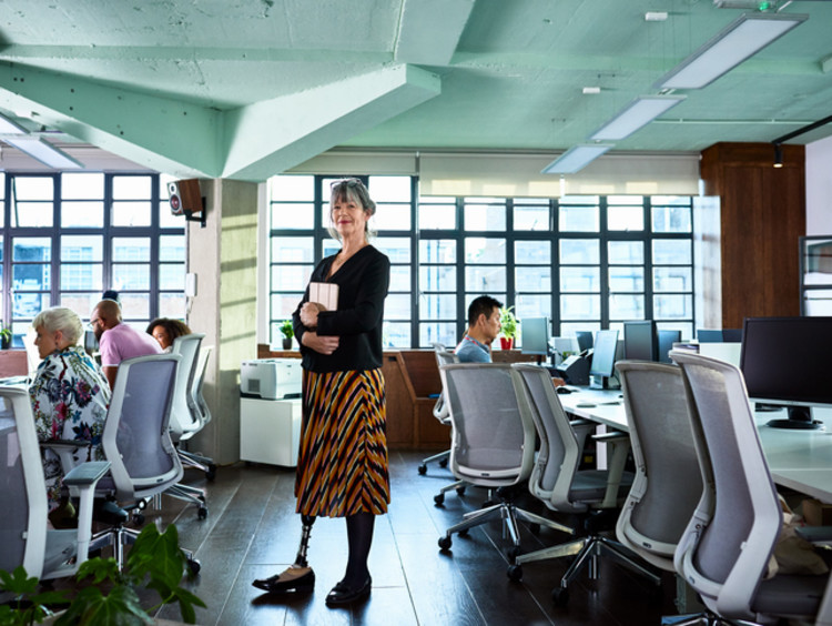 Woman standing in a room with with employees