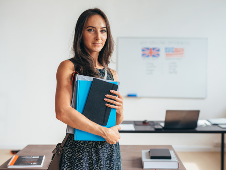 Spanish teacher standing in classroom with books beside whiteboard