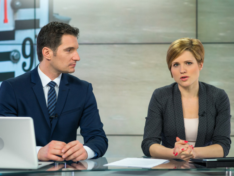 Two broadcast news analysts giving the news
