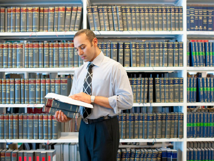 Man reading legal text in law library