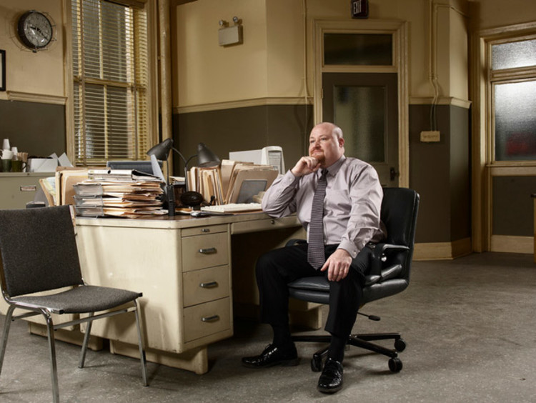 Private investigator sitting at desk covered in paperwork