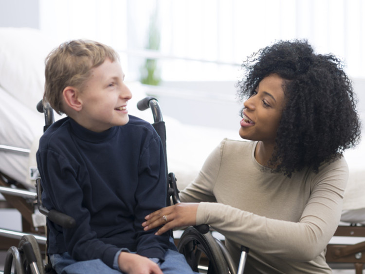 Female social worker talking with a child in a wheelchair