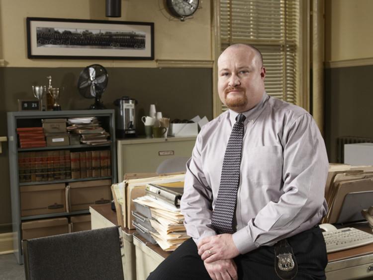 private investigator sitting on desk in office