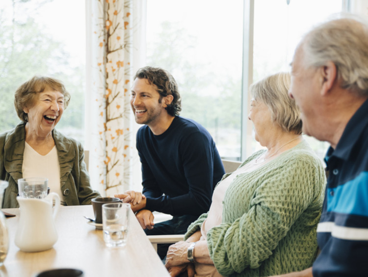 social worker and clients laughing at a table