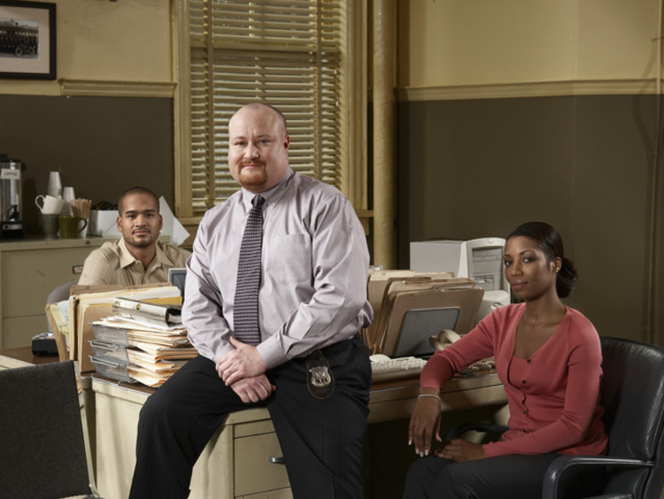 male and female criminal justice professionals smiling in office