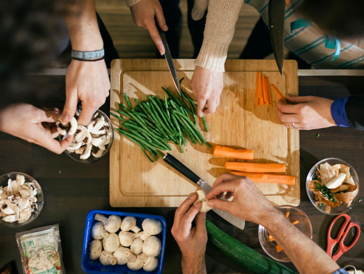 diverse hands prepare food around a cutting board in kitchen setting