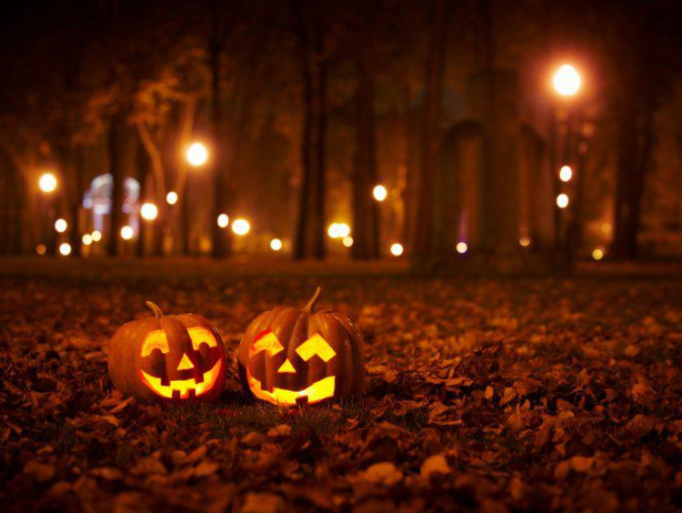 Jack-O-Lanterns lit on a dark road with fall leaves