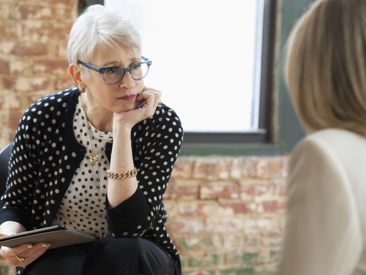 Career counselor with tablet in hand sitting across from client