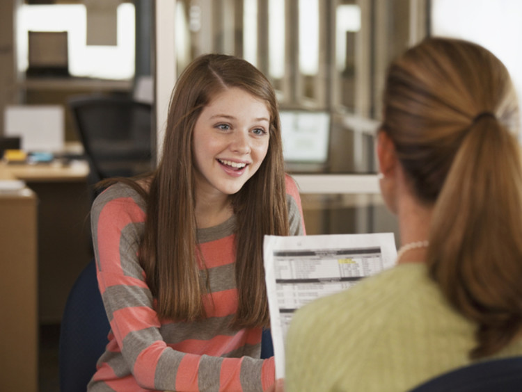 Female student with brown hair and striped shirt talking to her school counselor