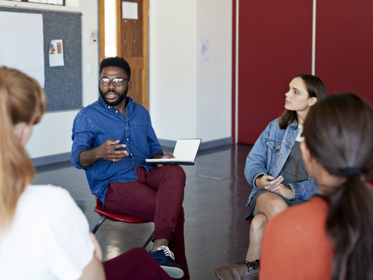 mental health professional with a psychology degree advising students in group session