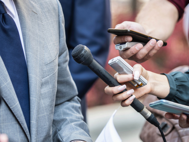 broadcast journalists hold microphones in front of a business man conducting a press conference interview