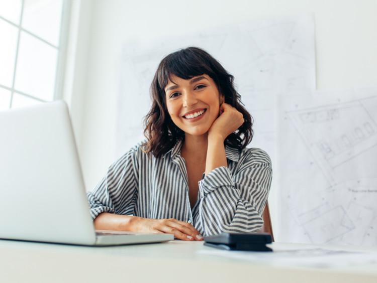 Entrepreneur on laptop smiling