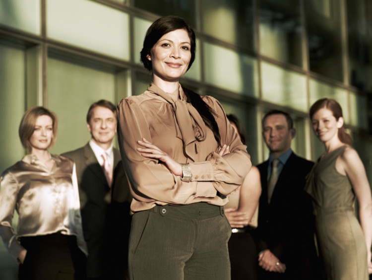 Woman stands confidently in front of her team