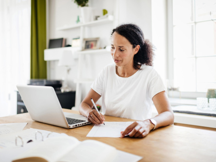 Female doctoral student working towards her online PhD on a laptop