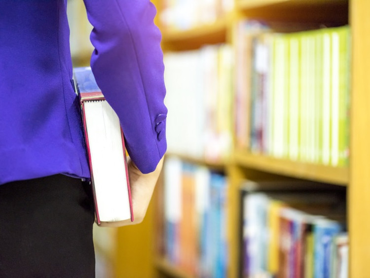 Researcher holding a textbook in a library
