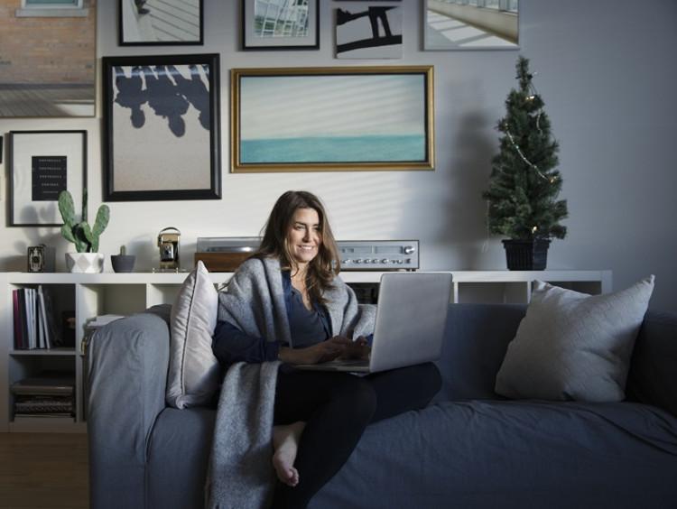 Woman working on laptop in pajamas