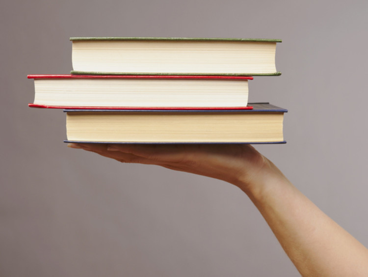 A hand holding up three books