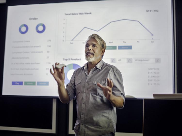 A male professor giving a lecture on quantitative data
