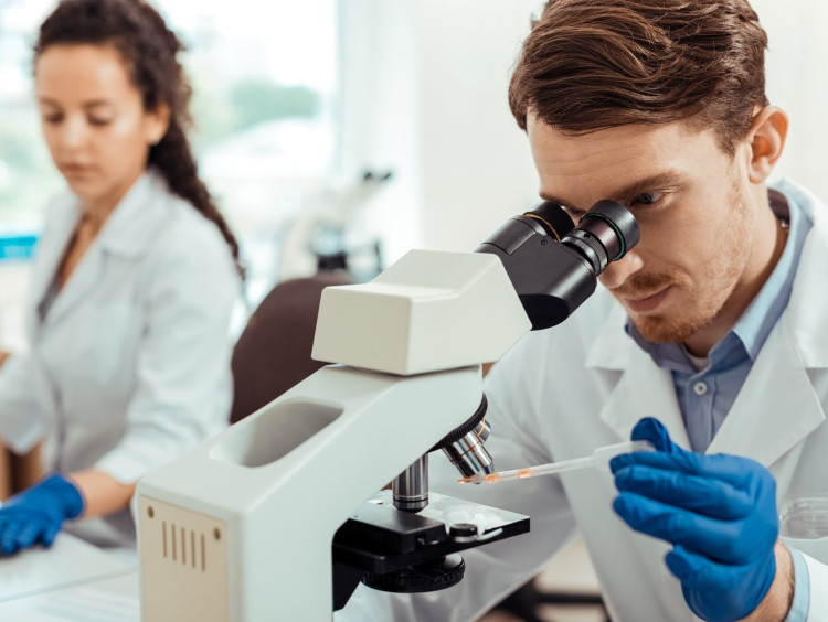 Biologist studies sample through a microscope in a lab