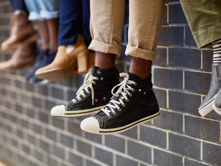 Picture of shoes of students sitting on a wall making friends