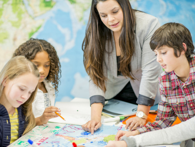 A history teacher helping her students find locations on a map