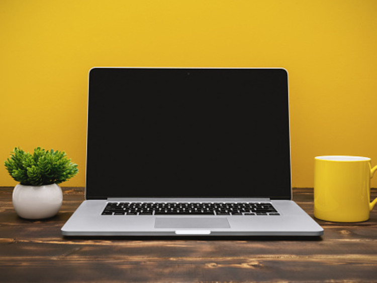 A student's laptop against a yellow background