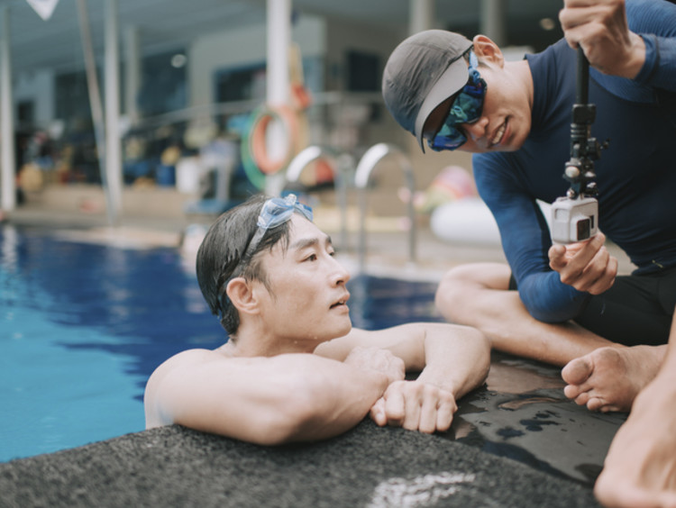Athletic trainer helping swimmer prevent injuries