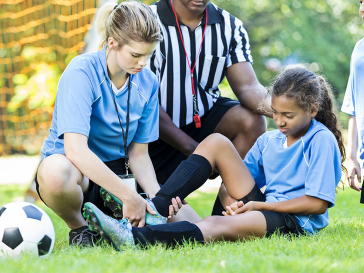 Athletic trainer aiding female athlete with referee