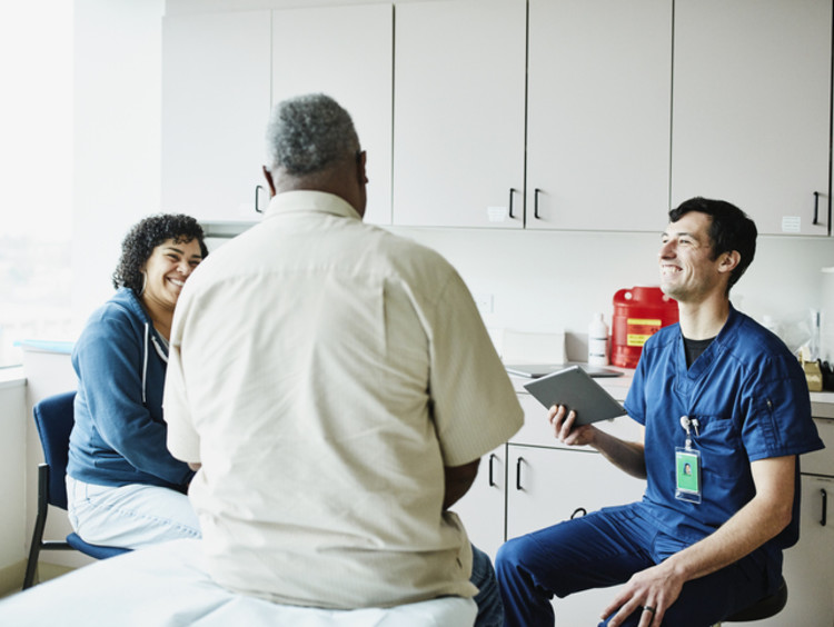 APRN talking with a patient in office