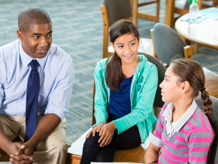 two teachers talking with a student who has been bullied