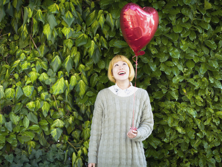 Asian woman with a blonde wig looks up at the heart-shaped balloon she's holding
