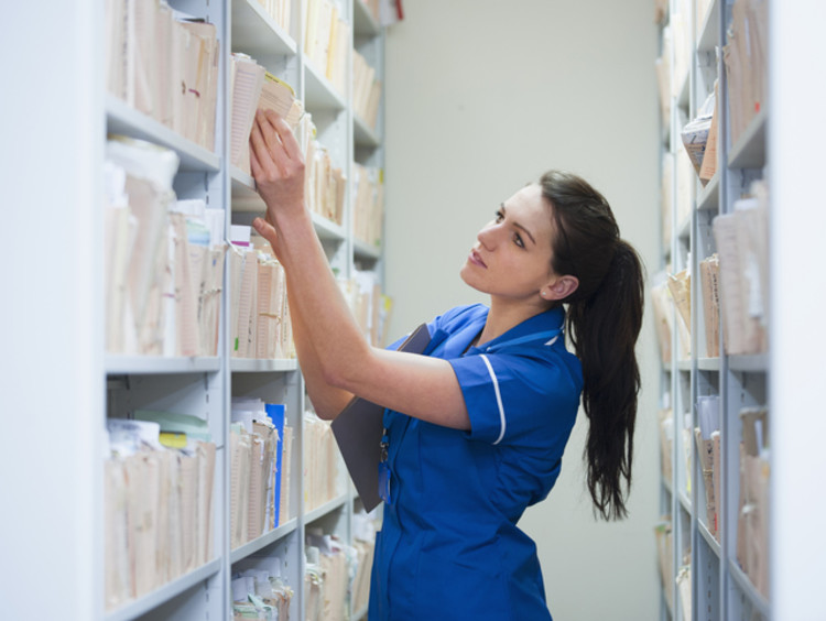 A healthcare administrator looking through medical files