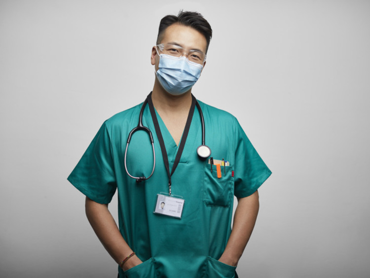headshot of male nurse wearing mask and scrubs