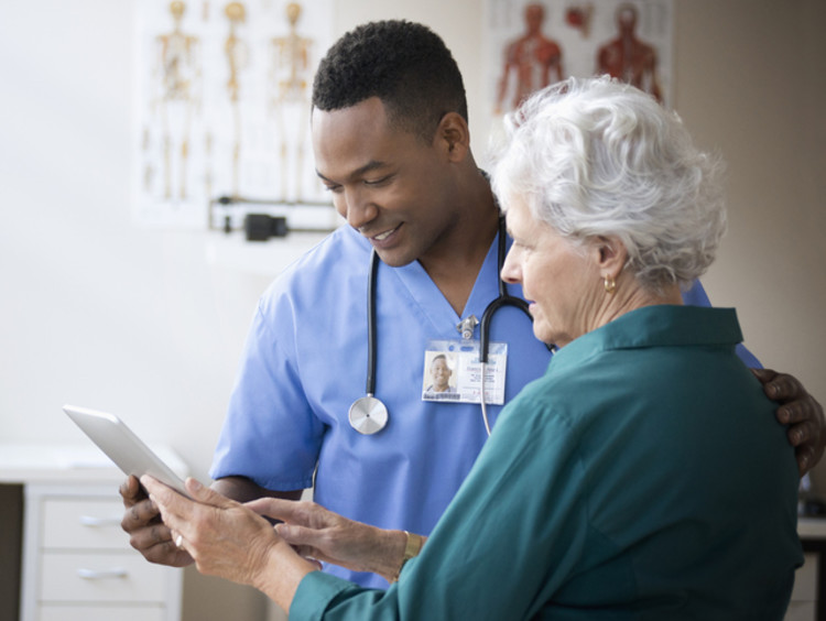 Male nurse reviewing information with elderly female patient.