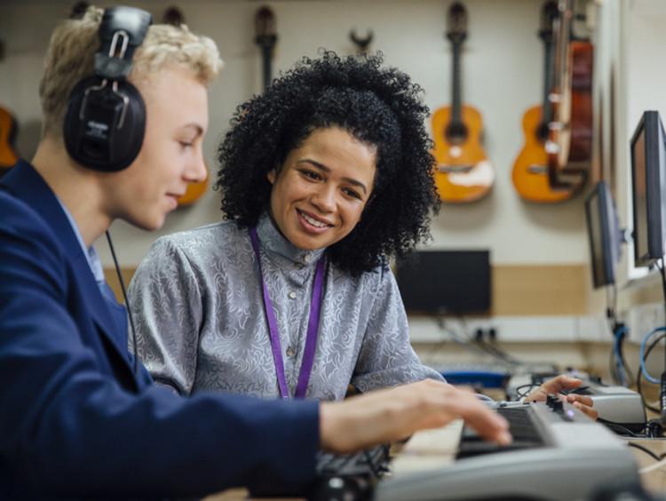 School music teacher helping student learn keyboard