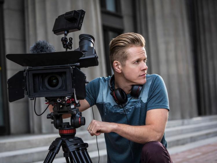 man kneeling next to a camera during filming