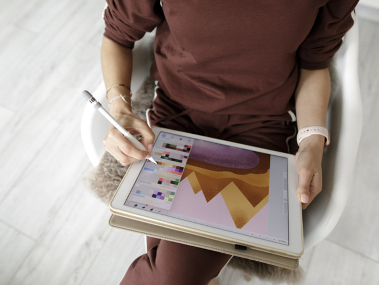 a student doing graphic design work on a tablet device