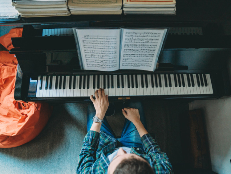 student with music degree playing piano