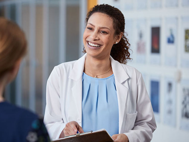 Women's Health Administrator discusses with a patient in clinical setting