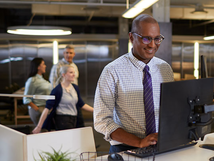man with accounting degree smiles while working at computer