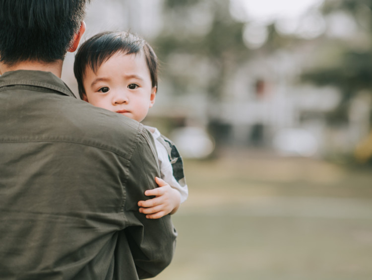 Father carrying Asian baby in his arms